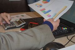 Business man doing finances on calculate analysis working with financial results Financial accounting sales forecast graph. Businessman Calculating Invoices Stock Images