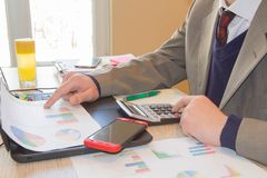Business man doing finances on calculate analysis working with financial results Financial accounting sales forecast graph. Businessman Calculating Invoices Stock Photography