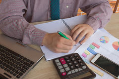 Business man doing finances on calculate analysis working with financial results Financial accounting sales forecast graph. Businessman Calculating Invoices Stock Image