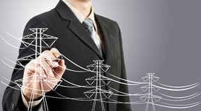 Business man drawing electric pylon and wire Royalty Free Stock Photos
