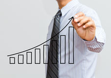 Business man drawing a growing graph. Business man drawing growing graph on screen Royalty Free Stock Photo