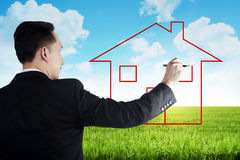 Business man drawing house on the meadow Stock Photo