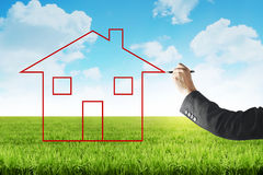 Business man drawing house on the meadow Stock Images
