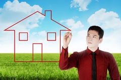 Business man drawing house on the meadow Royalty Free Stock Photography