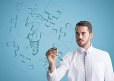 Business man drawing jigsaw doodle against blue background Royalty Free Stock Image