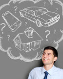 Business man dreaming of buying house, car or gadget Royalty Free Stock Images