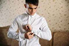 A business man dresses for work. A concentrated guy dresses cufflinks on his white shirt. Dark-haired model in a stylish. Shirt Stock Images