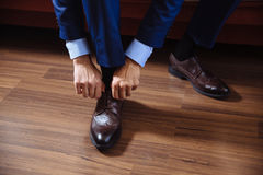 Business man dressing up with classic, elegant shoes. Groom wearing on wedding day, tying the laces and preparing. Stock Photo