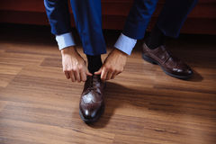 Business man dressing up with classic, elegant shoes. Groom wearing on wedding day, tying the laces and preparing. Royalty Free Stock Image