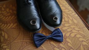 Business man dressing up with classic, elegant shoes. Groom wearing shoes on wedding day, tying the laces and preparing. The bridegroom is dressing for wedding stock footage