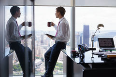 Business Man Drinking Coffe And Reading News On Tablet Stock Image