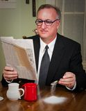 Business Man Drinking Coffee. Humorous scene of a business man dressed in a suit and tie sitting down to morning coffee reading the newspaper and absentmindedly Stock Photo
