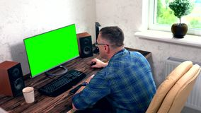 Business man drinking coffee and working. On a large desktop computer in an office viewed high angle from behind stock video footage