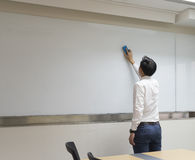 Business man duster white board in meeting room.  Royalty Free Stock Photo