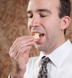 Business Man Eating Orange. Closeup view of a young businessman eating an orange slice Stock Photos
