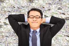 Business man enjoying and lying on the money stock images