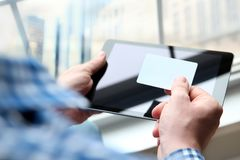Business man entering data of a credit card . On-line shopping on the internet using a digital tablet.  Stock Photography
