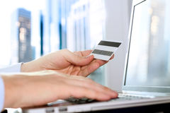 Business man entering data of a credit card . On-line shopping on the internet using a laptop Stock Images