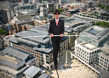 Business man in equilibrium on a rope over a city. Wearing a suit and hat Stock Images
