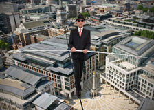 Business man in equilibrium on a rope over a city Stock Photography