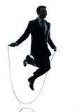 Business man exercising jumping rope silhouette. One  businessman exercising jumping rope in silhouette studio isolated on white background Royalty Free Stock Photo