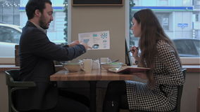 Business man explain diagram to assistant at lunch in cafe stock footage