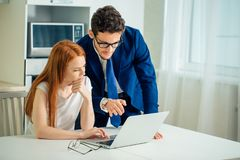 Business man explaining something to woman with laptop. Business in suit men explaining something to women with laptop Stock Images