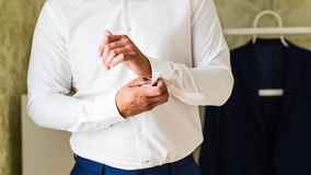 Business man fastening buttons on shirt sleeve at home close-up Royalty Free Stock Image