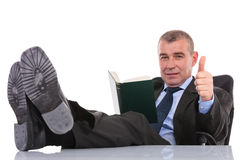 Business man with feet on desk holds a book and shows thumb up Royalty Free Stock Photos
