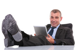 Business man with feet on desk holds his tablet Stock Image