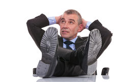 Business man with feet on desk looks away Royalty Free Stock Photo