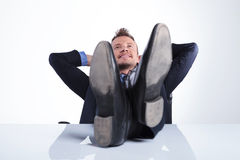 Business man with feet on desk. Young business man holding his feet on the desk and his hands behind his head while smiling away from the camera. on a light gray Royalty Free Stock Image