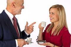 Business man & female conversation. Senior businessman having a conversation with a young blonde female drinking an espresso and smiling (isolated on white Royalty Free Stock Photo