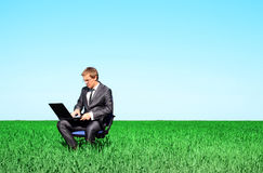 Business man on a field on a laptop Royalty Free Stock Photography