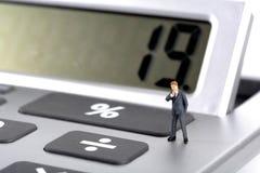 Business man figurine standing on calculator Royalty Free Stock Photo