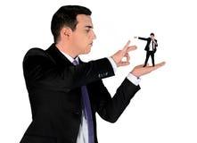 Business man finger flipping on little man Stock Photo