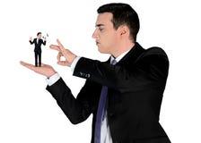 Business man finger flipping on little man Stock Images