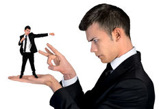 Business man finger flipping on little man Royalty Free Stock Image