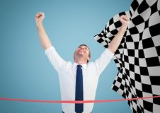 Business man at finish line against blue background and checkered flag. Digital composite of Business man at finish line against blue background and checkered Royalty Free Stock Photo