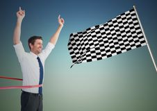 Business man at finish line against blue green background and checkered flag. Digital composite of Business man at finish line against blue green background and Stock Images