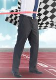 Business man at finish line on track against sky and checkered flag. Digital composite of Business man at finish line on track against sky and checkered flag Stock Photography