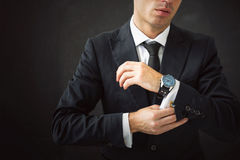 Business man fixing his shirt. With cuff-link Stock Photos