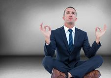 Business man with flare meditating in grey room Royalty Free Stock Image