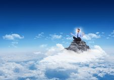 Business man with flare meditating on mountain peak in the clouds with blue sky. Digital composite of Business man with flare meditating on mountain peak in the Stock Photos