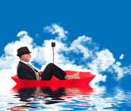 Business man floating on umbrella Stock Images