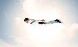 Business man flying like a superhero in clouds on the sky Stock Photos