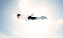 Business man flying like a superhero in clouds on the sky Stock Image