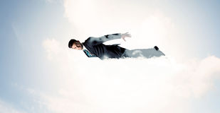 Business man flying like a superhero in clouds on the sky Stock Images