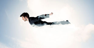 Business man flying like a superhero in clouds on the sky Royalty Free Stock Images