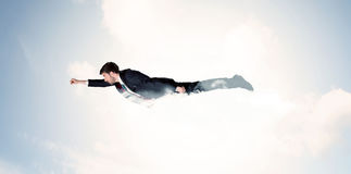 Business man flying like a superhero in clouds on the sky Royalty Free Stock Photography